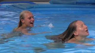 Two beautiful girls swimming and licking by the pool